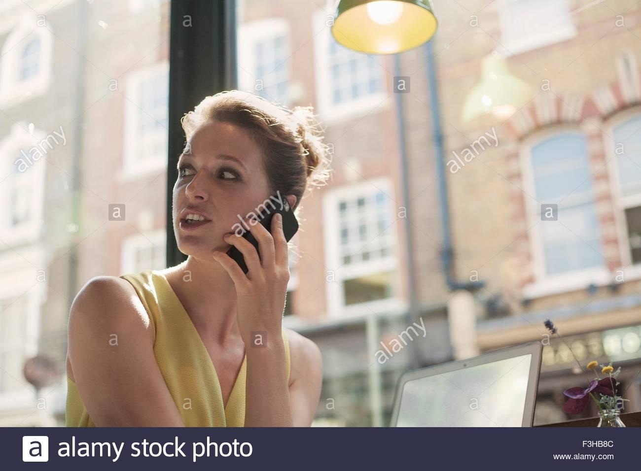 Eine junge Brünette Frau sitzt in einem Café mit Handy Stockbild