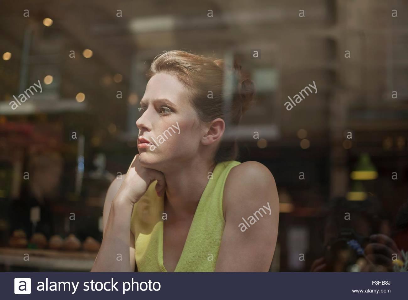 Eine junge Brünette Frau sitzt in einem Café, Blick aus dem Fenster Stockbild