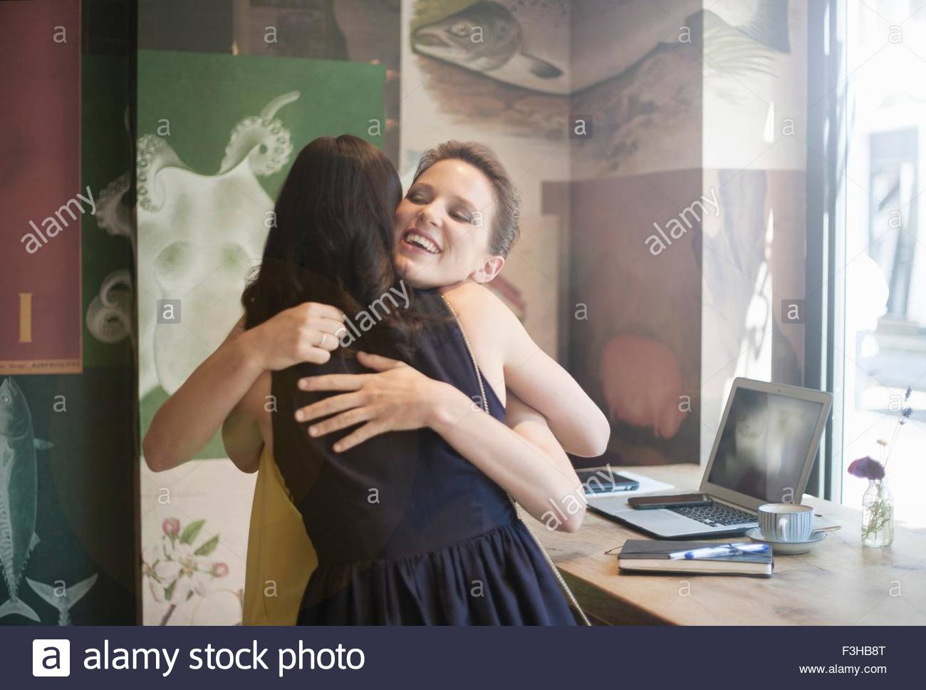 Zwei junge Brünette-Frauen sitzen in einem Café Gruss einander mit einer Umarmung Stockbild