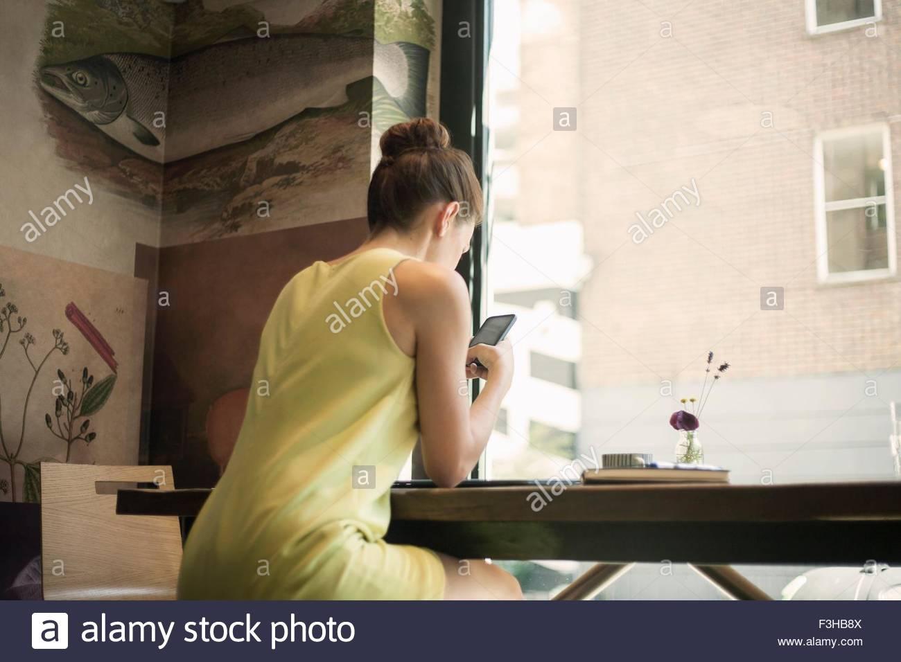 Eine junge Brünette-Frauen sitzen in einem Café SMS und halten Handys Stockbild