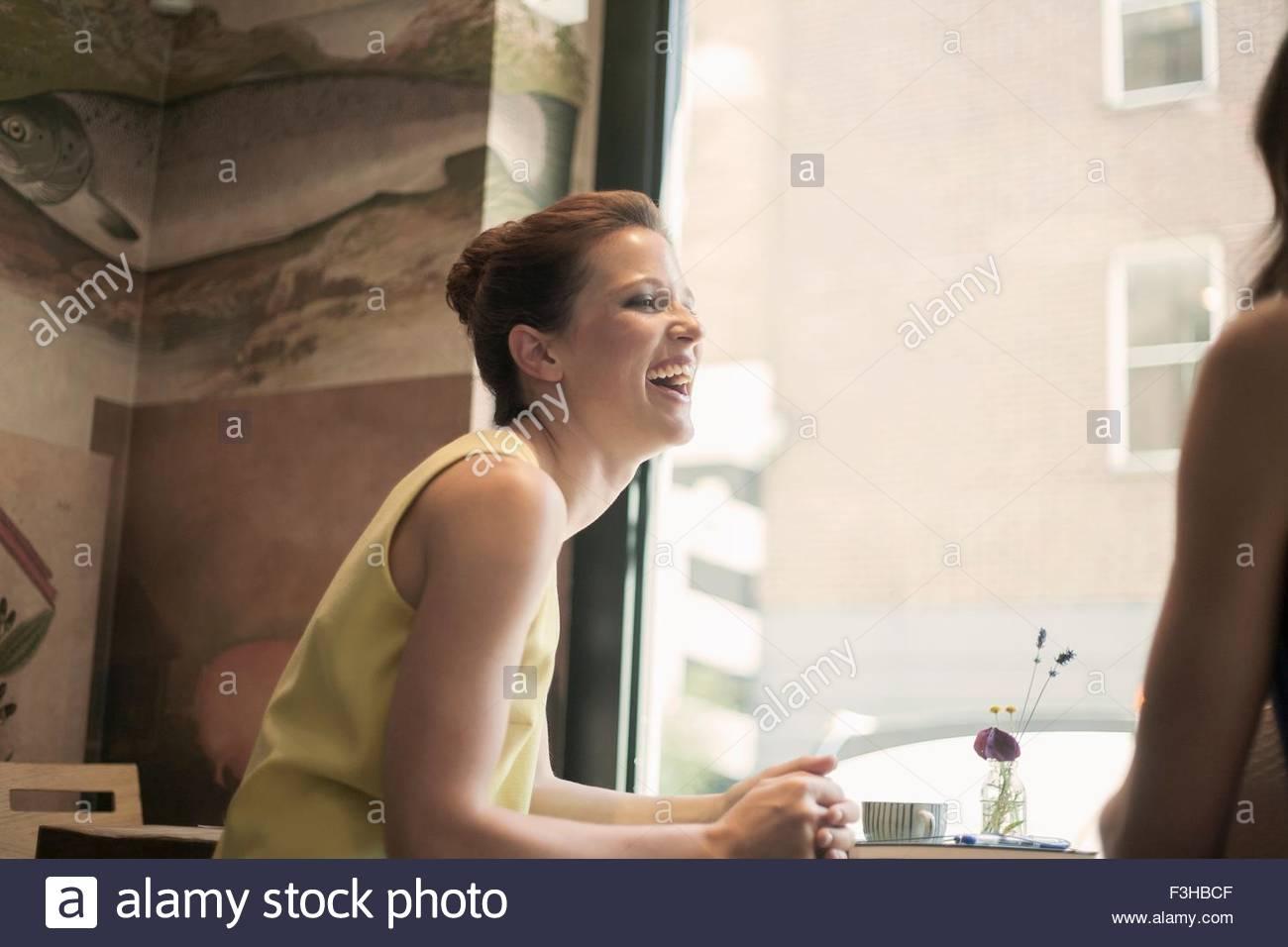 Zwei junge Brünette-Frauen sitzen in einem Café, reden und lachen Stockbild