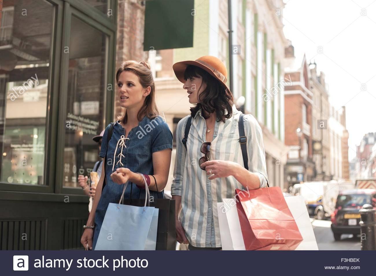 Zwei Frauen, die Schaufenster betrachten Einkaufstaschen tragen Stockfoto