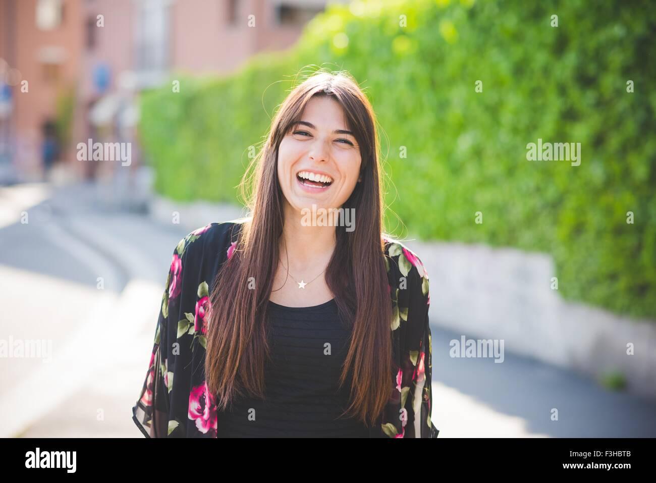 Porträt der jungen Frau mit langen braunen Haaren lachen Stockbild