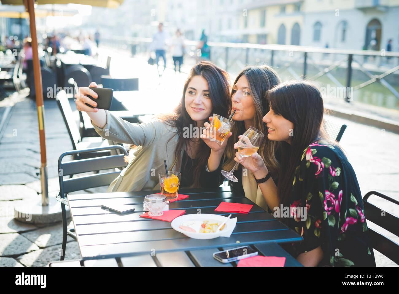 Drei junge Frauen posieren für Smartphone Selfie im Waterfront café Stockbild