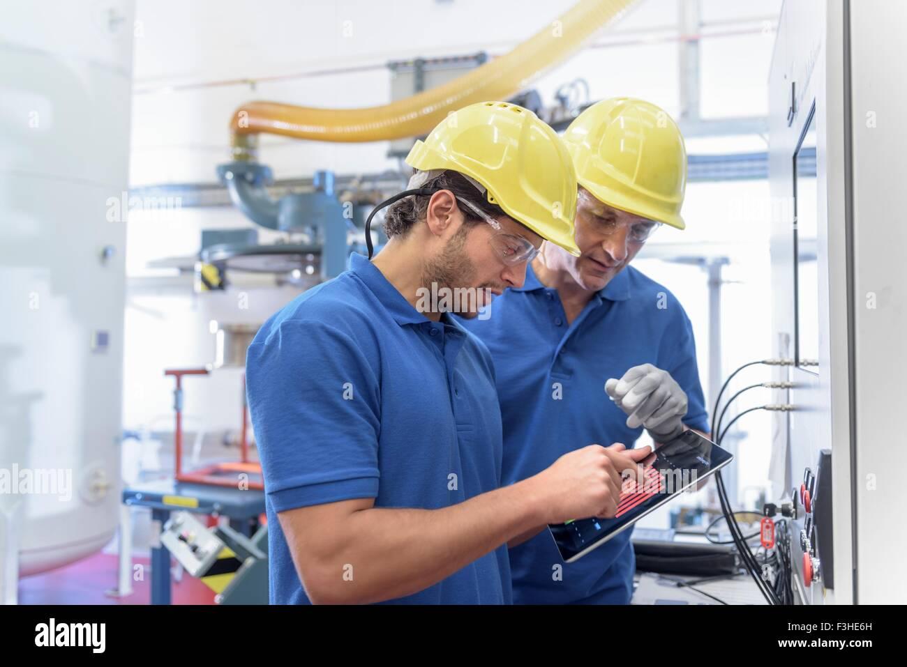 Arbeiter, die Umwelt Prüfgeräte mit digital-Tablette in Elektronik-Fabrik in Betrieb Stockbild