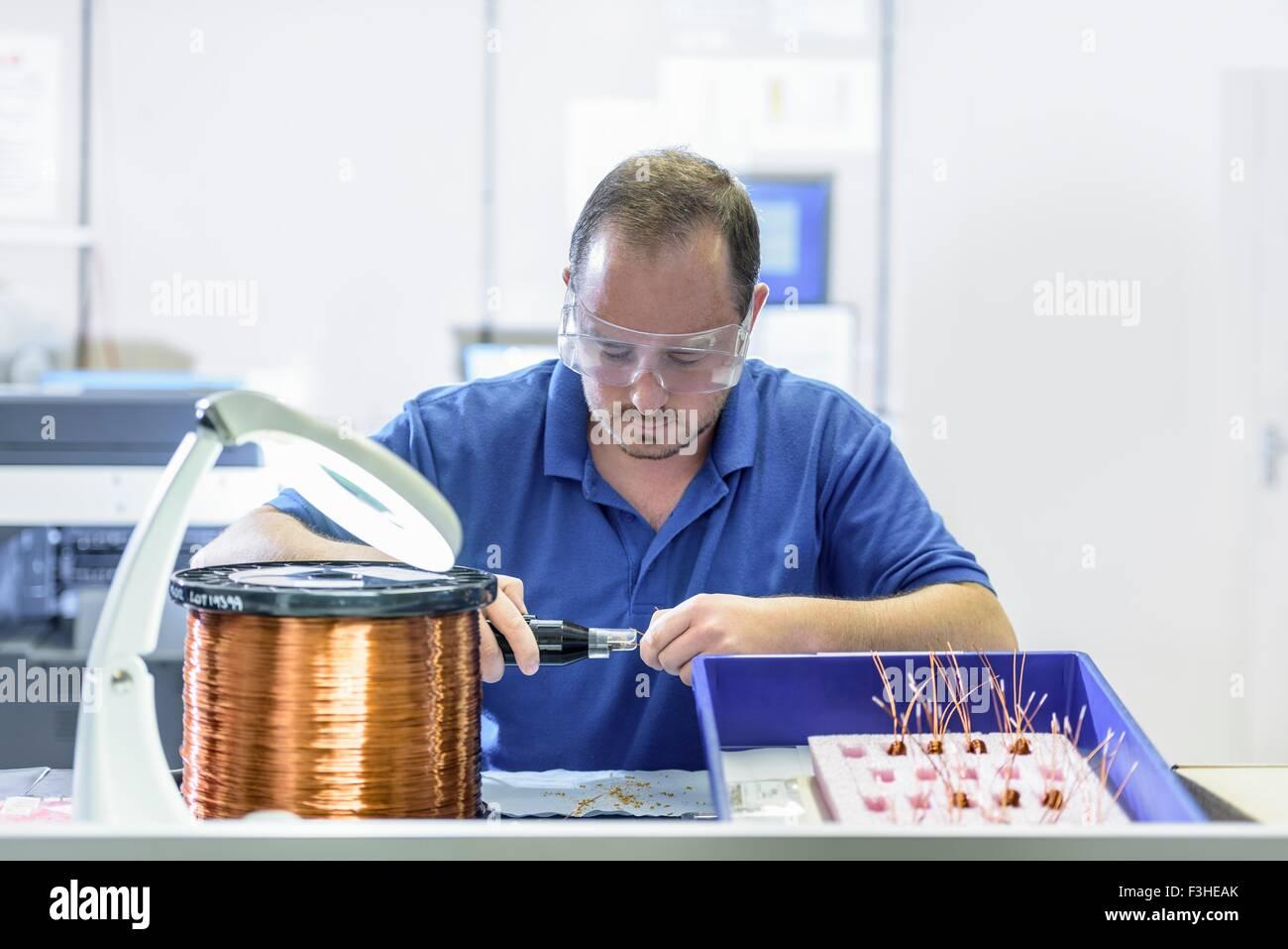 Männliche Arbeiter, die Montage von elektromagnetischer Spulen in Elektronik-Fabrik Stockbild