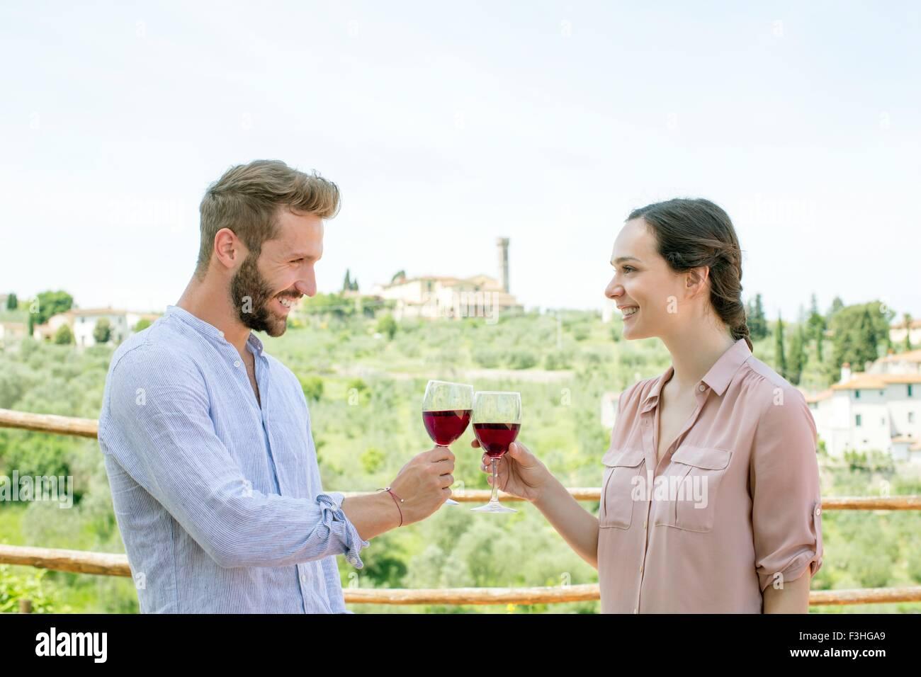 Taille bis Seitenansicht des junges Paar macht einen Toast lächelnd von Angesicht zu Angesicht Stockbild