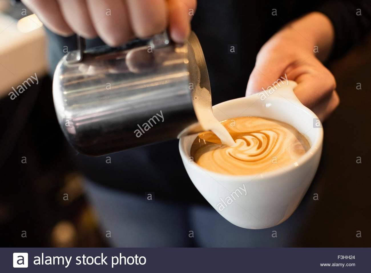 Café Barista Gießen Milch in Kaffee, Mittelteil, Nahaufnahme Stockbild