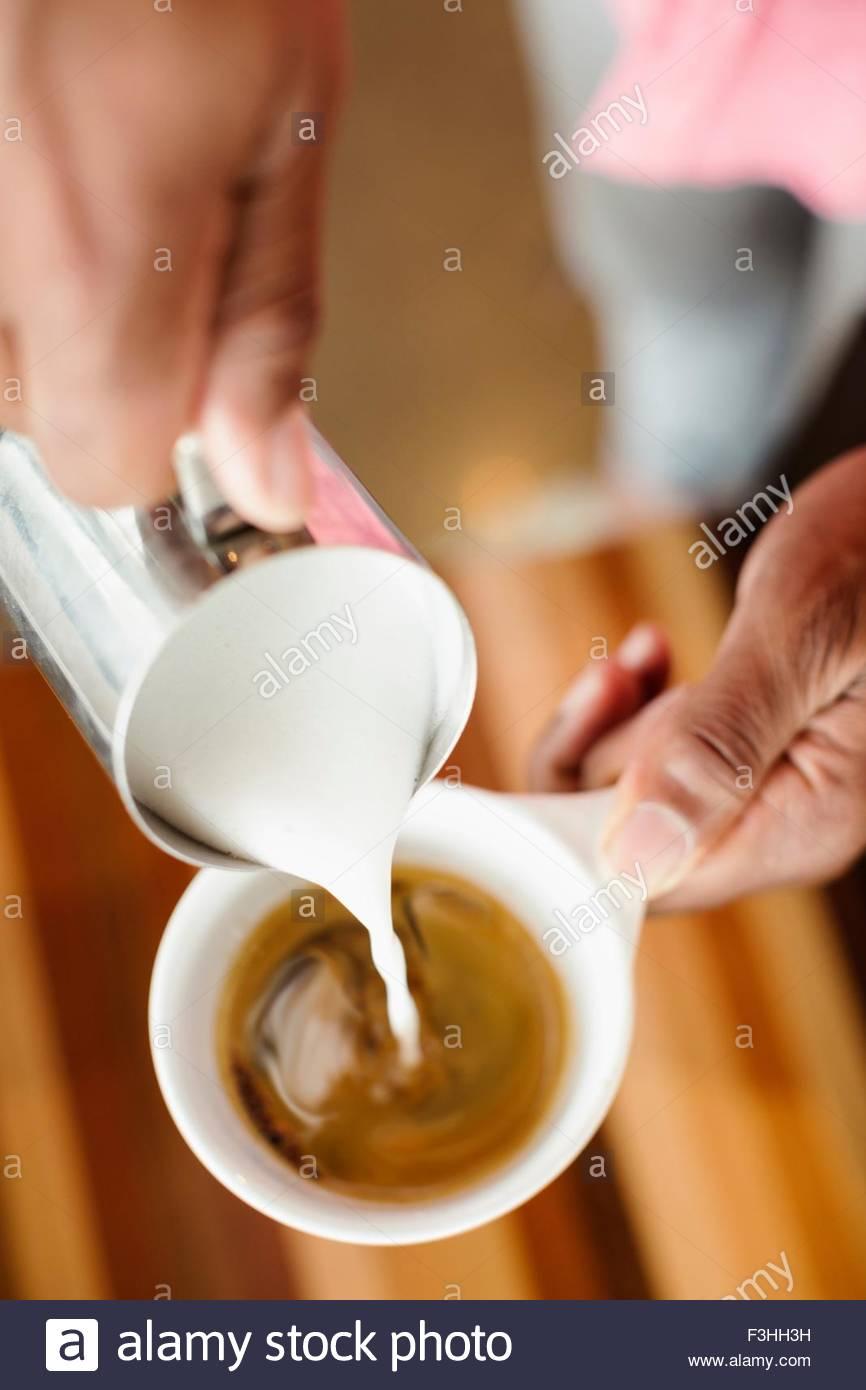Café Barista gießt Milch in Kaffee, Nahaufnahme Stockbild