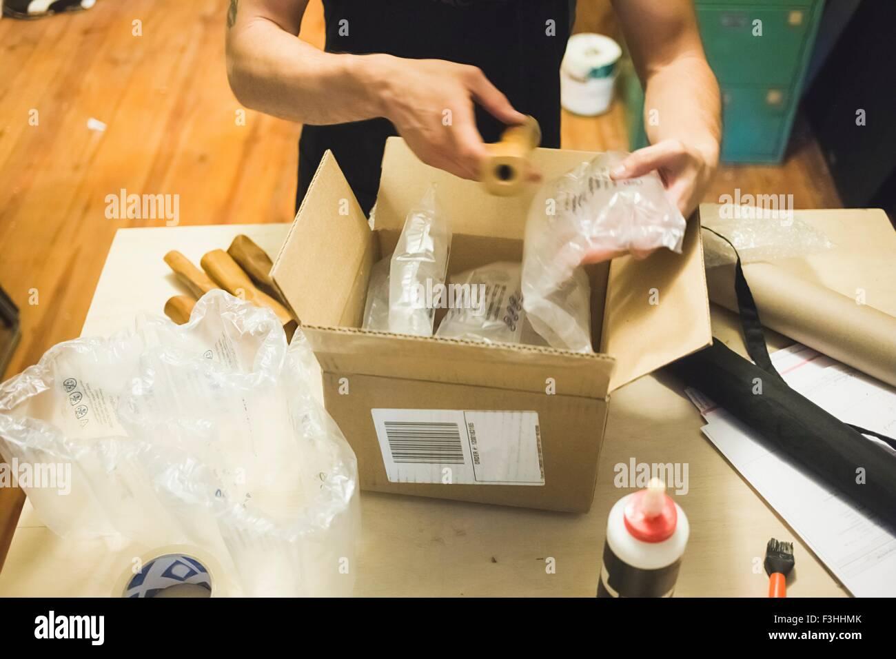 Erhöhte Ansicht der jungen mans Hände mit Luftpolsterfolie ein Paket Lieferung vorbereiten Stockbild
