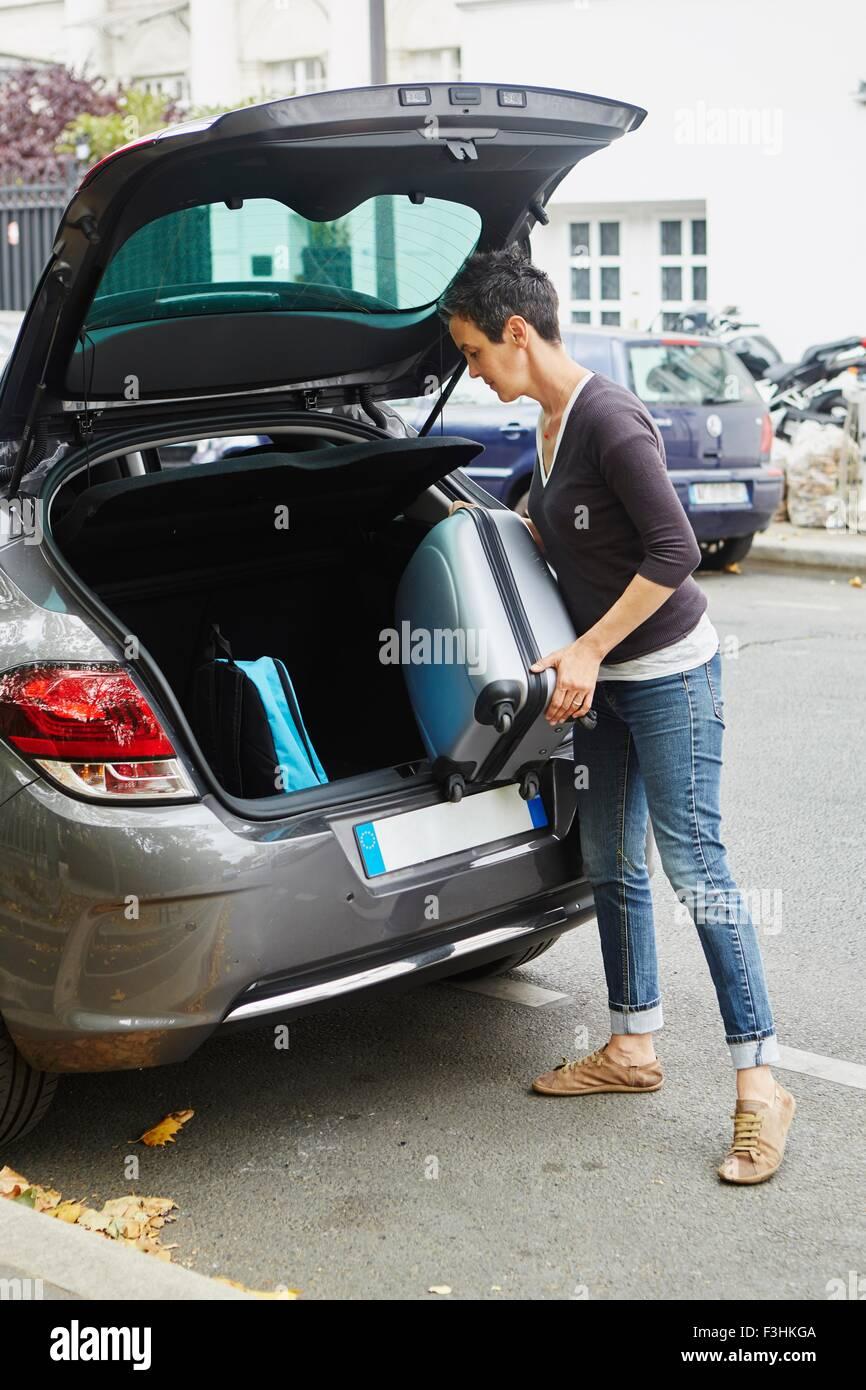 Frau stehend neben dem Auto, indem Koffer in offenen boot Stockfoto