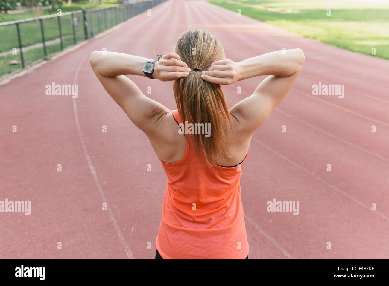 Junge Frau am Sportplatz, Rückansicht Ausführung vorbereitet Stockbild