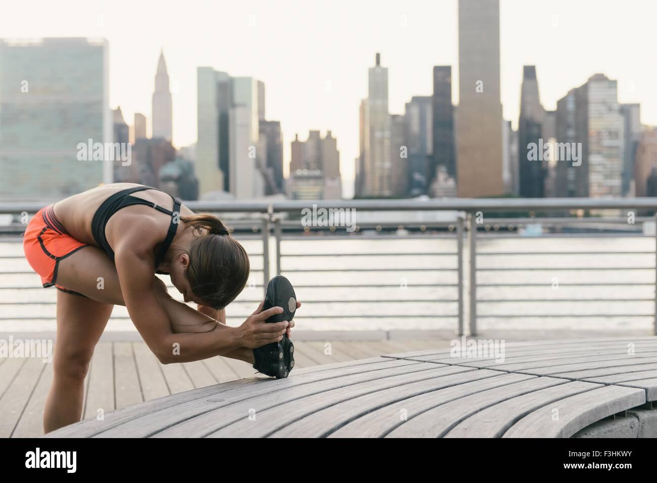 Junge Frau in Laufbekleidung neben Fluss stretching vor dem Training Stockfoto