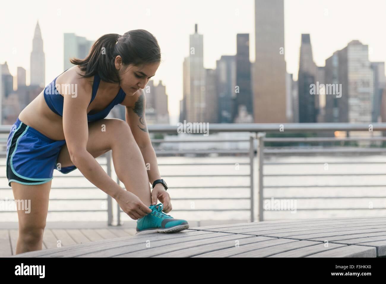 Junge Frau in Laufbekleidung neben Fluss ihre Schnürsenkel zu binden Stockfoto