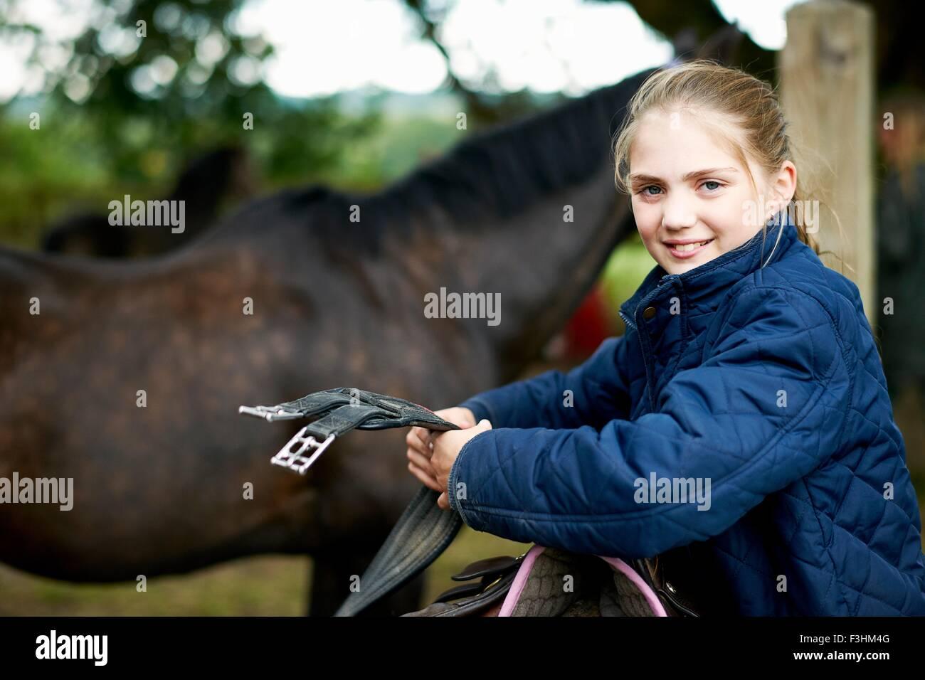 Mädchen-Reiterin Vorbereitung Sattel Stockbild