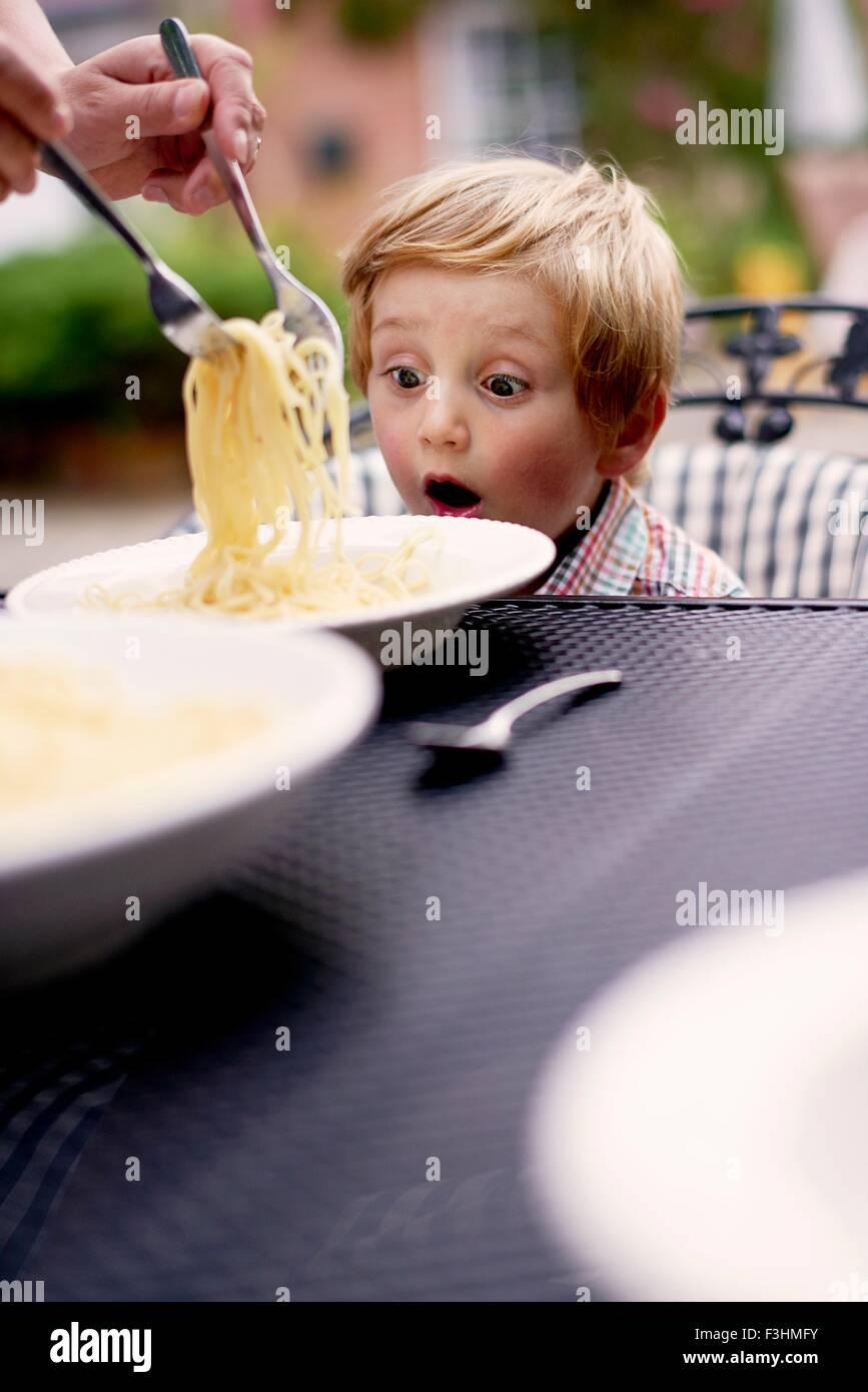 Jungen am Gartentisch versorgenden Spaghetti, sitzen suchen überrascht Stockbild