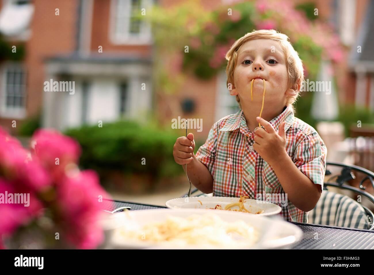 Junge sitzt am Gartentisch Aufsaugen von Spaghetti, Blick in die Kamera Stockbild