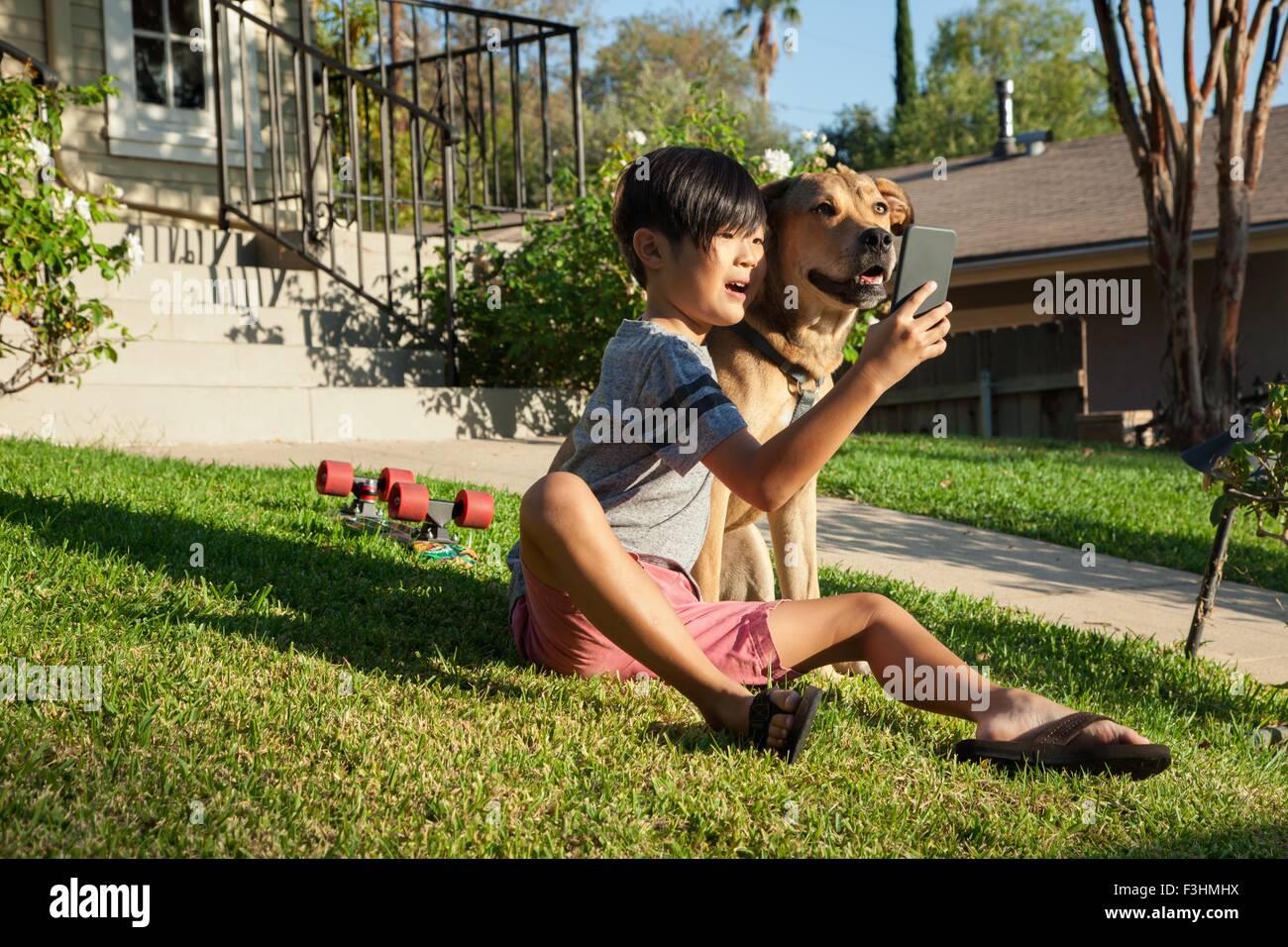 Junge posiert für Smartphone Selfie mit Hund im Garten Stockbild