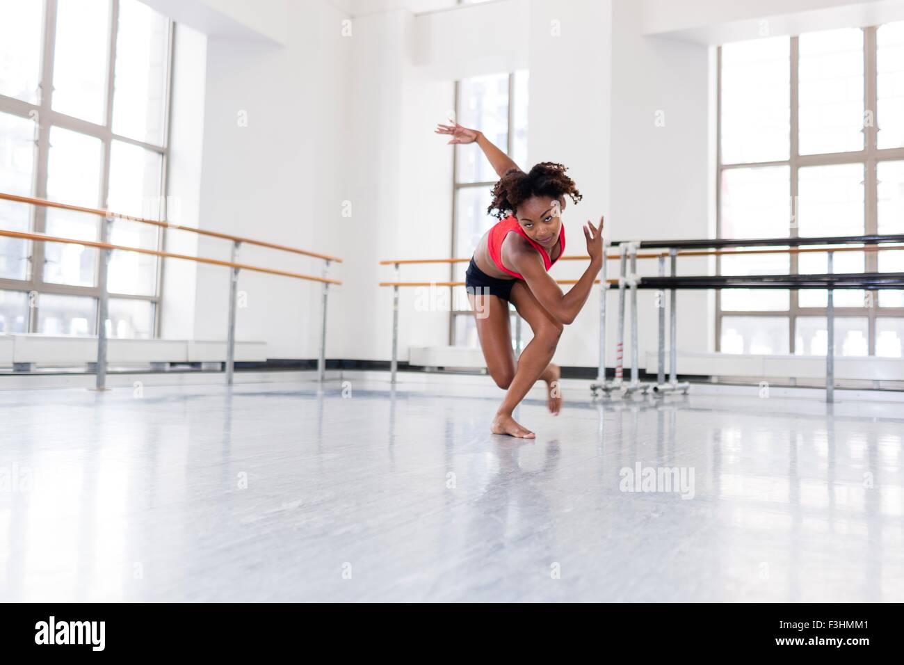 Junge Frau im Tanzstudio tanzen, Blick in die Kamera Stockbild