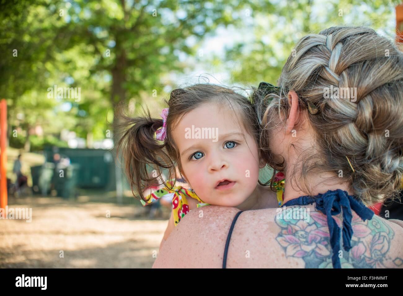 Babymädchen über Mütter Schulter in die Kamera schaut Stockbild
