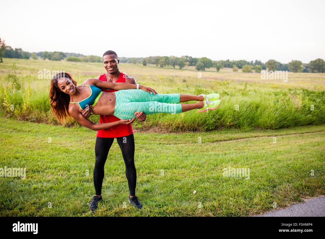 Junger Mann Training hält Freundin horizontal Stockbild