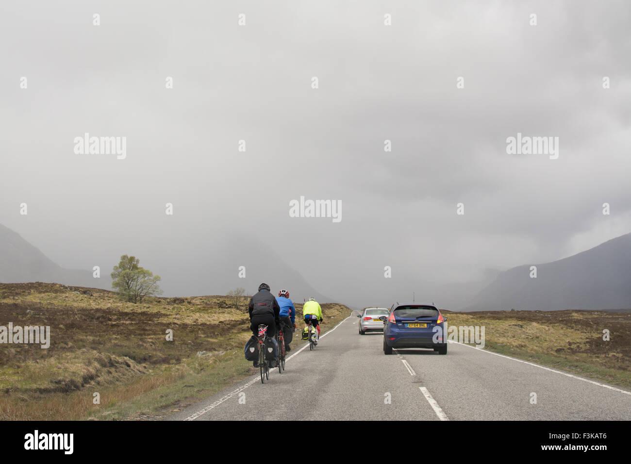 Autos, Radfahrer geben viel Platz wie sie auf der A82 Straße durch Glencoe, Scotland, UK überholen Stockbild