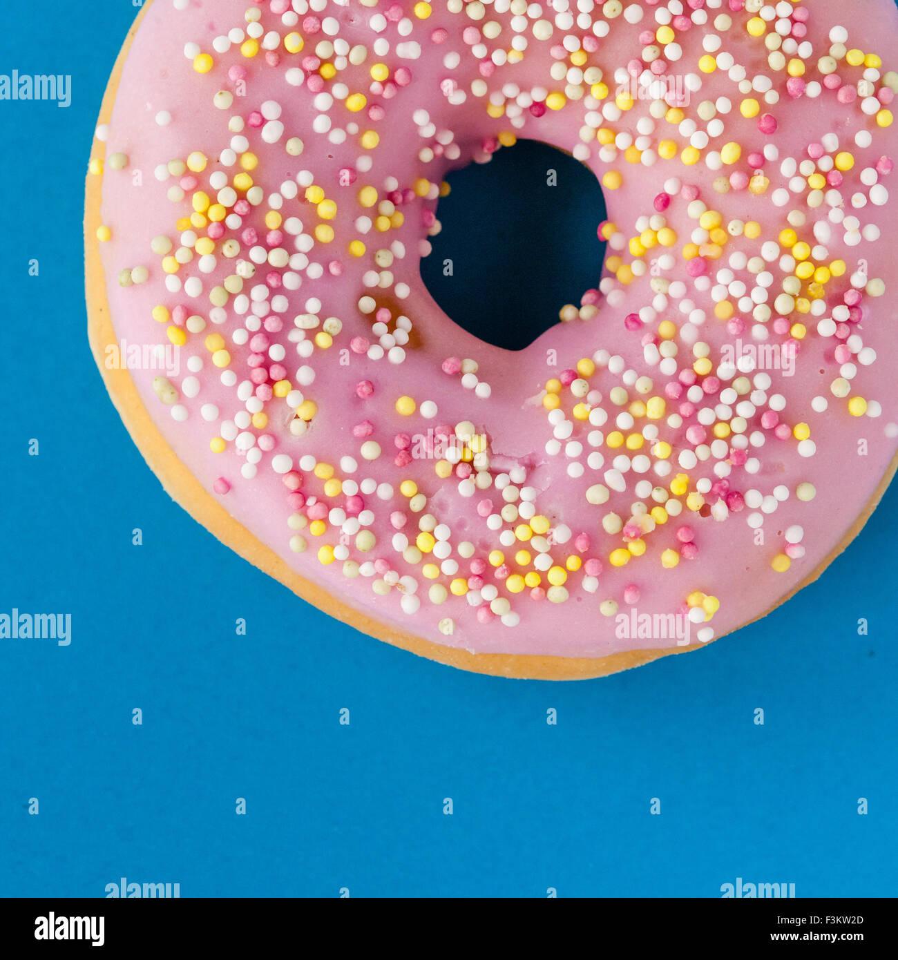 Donut mit rosa Zuckerguss und Streusel auf Türkis Hintergrund Stockbild