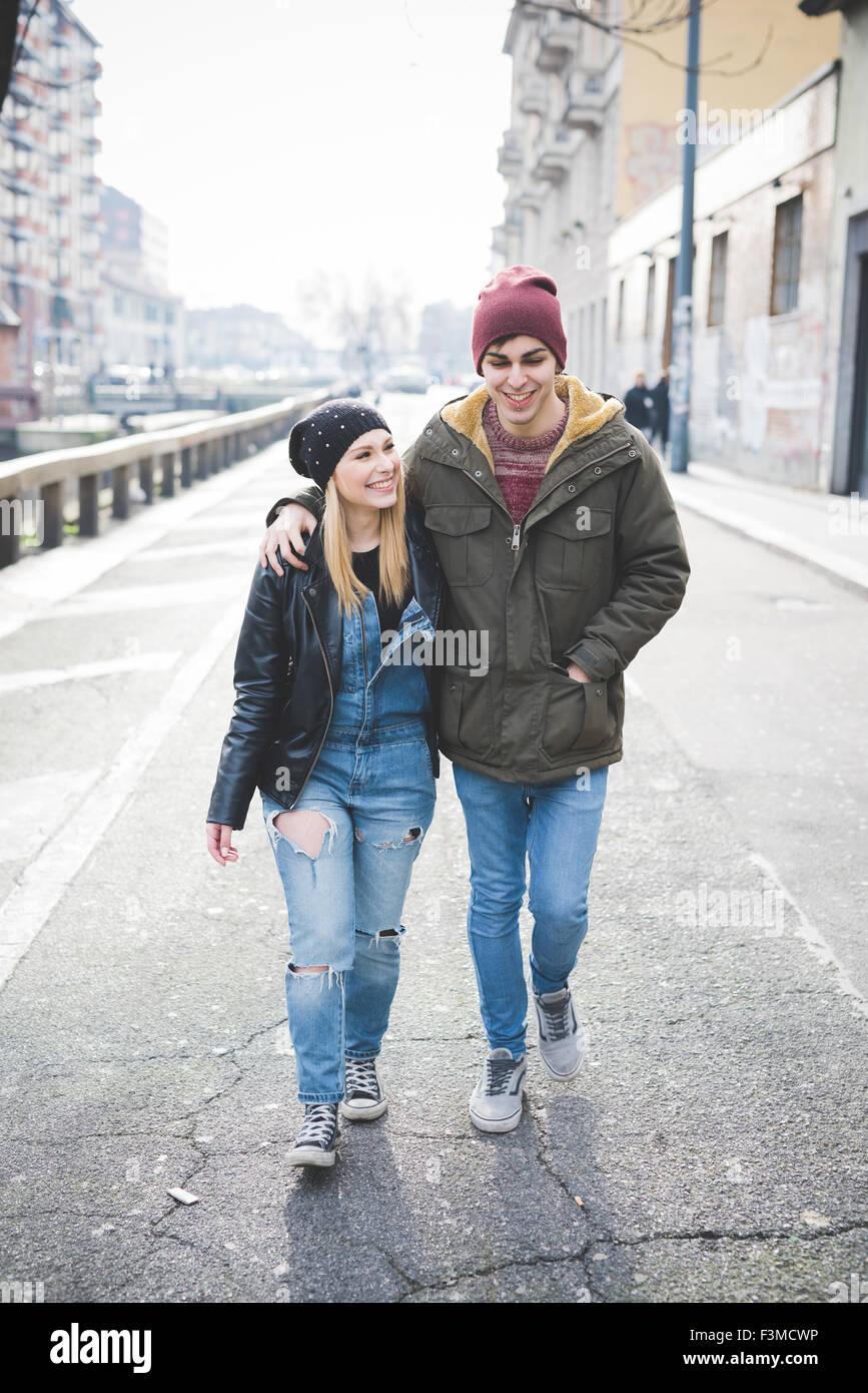 junge schöne Paar Liebhaber zu Fuß in die Stadt umarmt, sie ist links mit Blick auf, er schaut nach unten, Stockbild