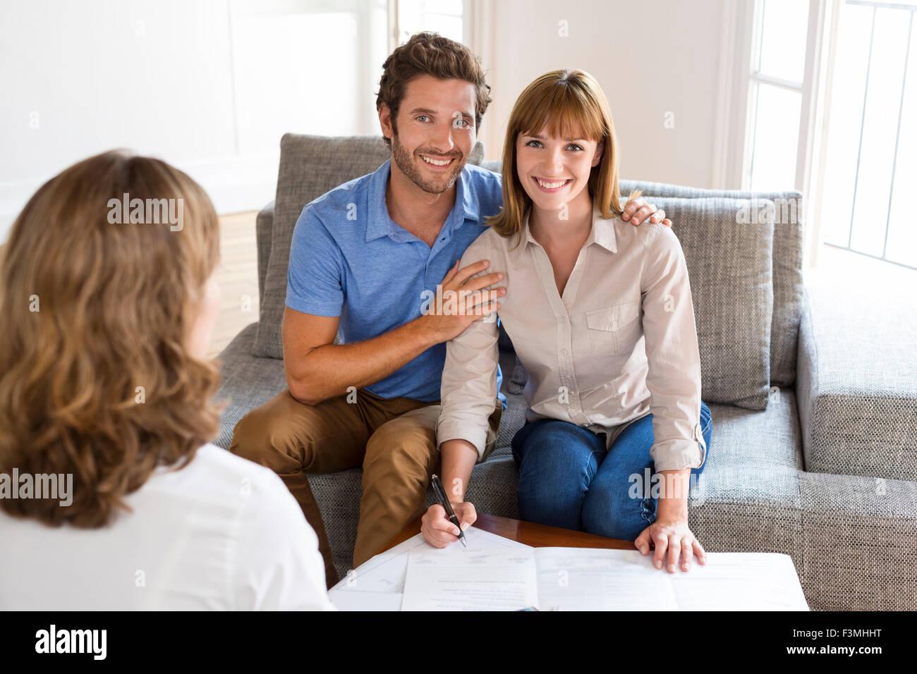 Junges Paar Besitzer Immobilienmakler für Haus-Investition zu treffen. Unterzeichnung eines Vertrages. Gesicht Stockbild