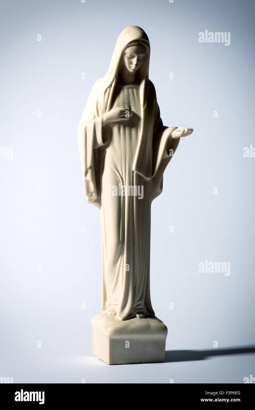 Statue der Jungfrau Maria auf einem grauen Hintergrund mit Demut und Liebe Stockbild