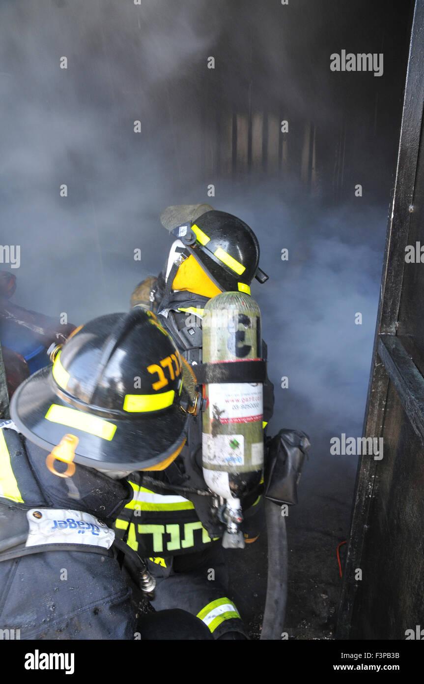 Feuerwehrleute mit Schutzausrüstung in einem verrauchten Raum Stockbild