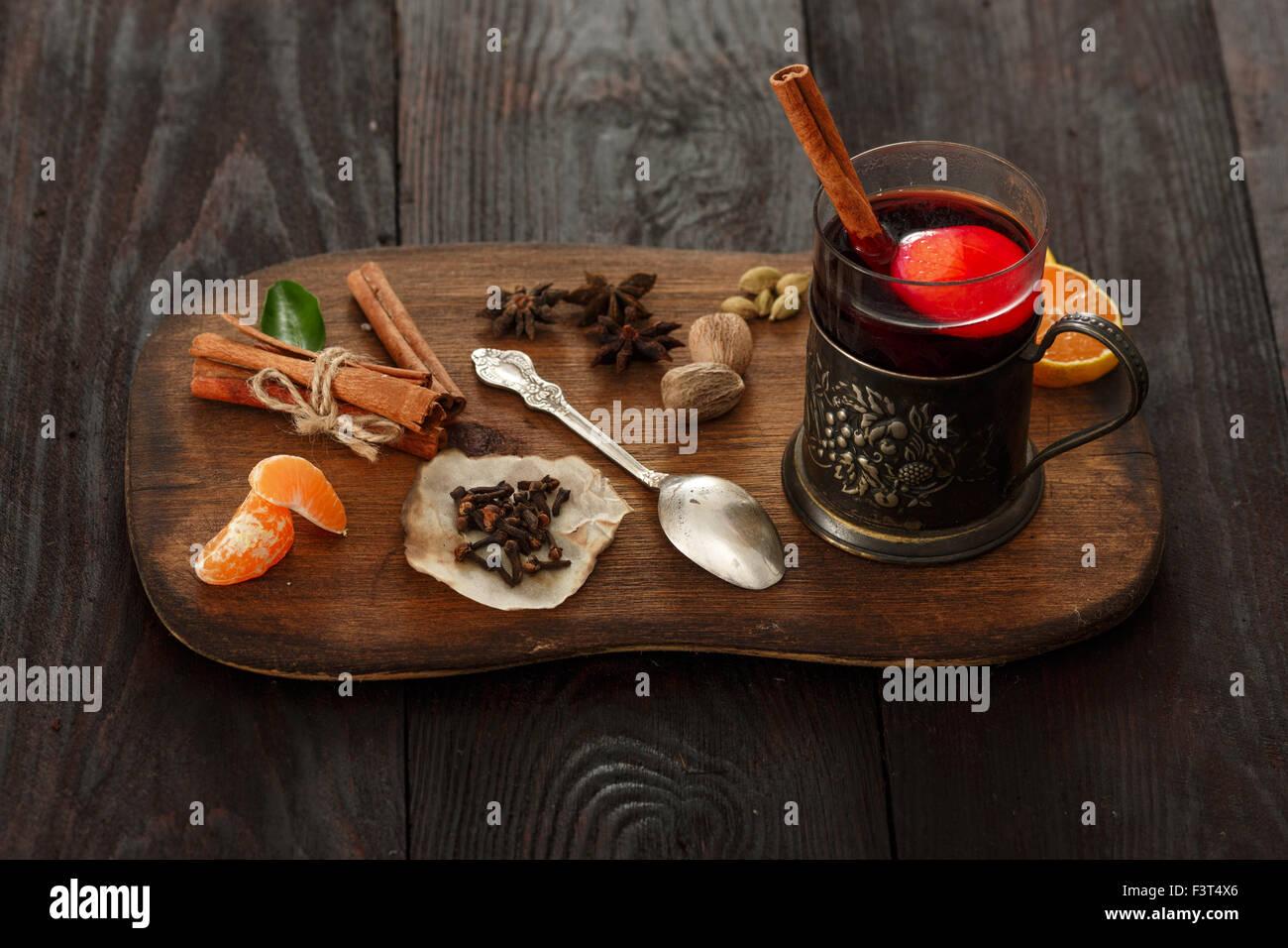 Glas Glühwein (Punch) in Glas-Halter über dunklen Holztisch auf Holzteller mit Gewürzen serviert. Stockfoto