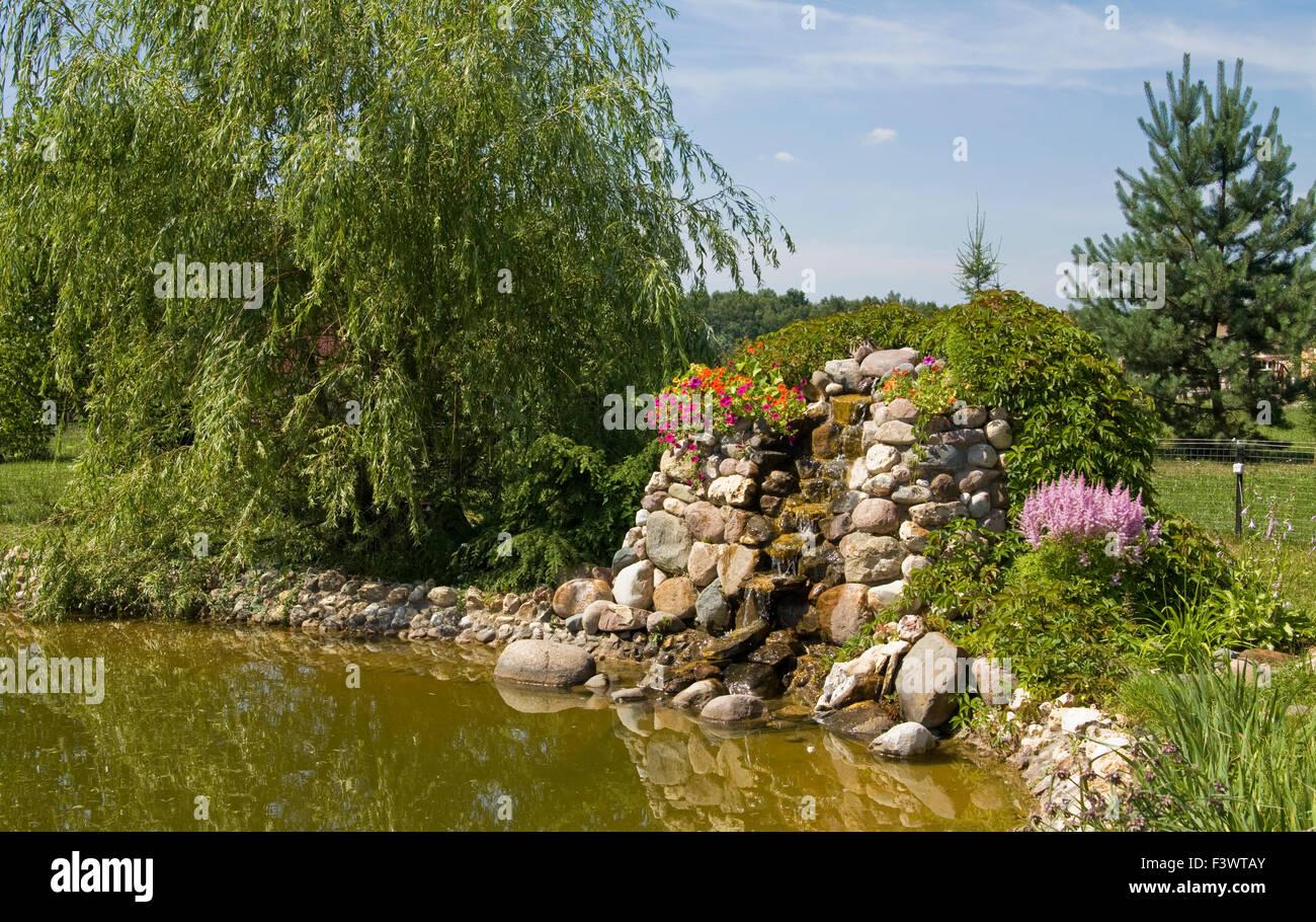 Beispiel der Landschaftsgestaltung für Garten - wenig künstlicher Wasserfall am Teich. Stockbild