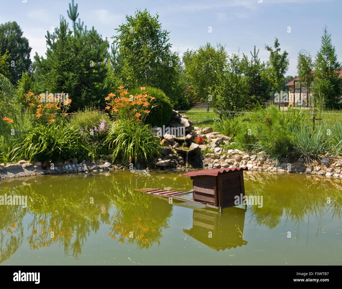 landschaftsgarten design kleiner wasserfall am teich im garten lilien und andere pflanzen. Black Bedroom Furniture Sets. Home Design Ideas