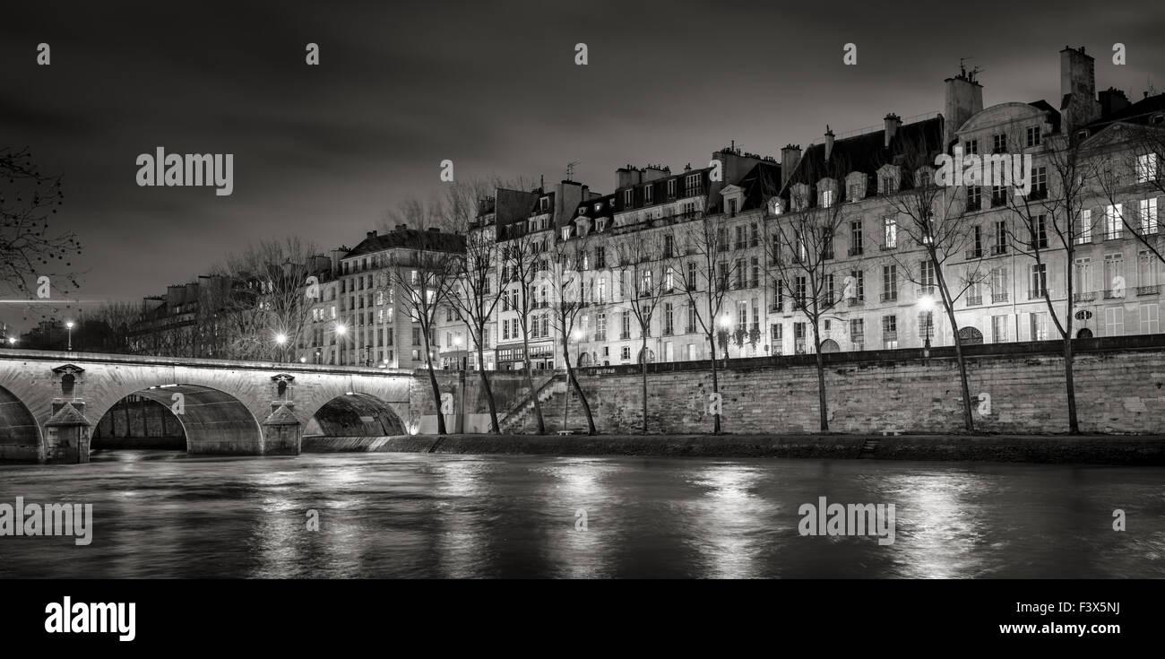 Seine River, Quai de Bourbon auf der Ile Saint Louis mit Pont Marie und abends Leuchten. Reihe von Gebäuden Stockbild