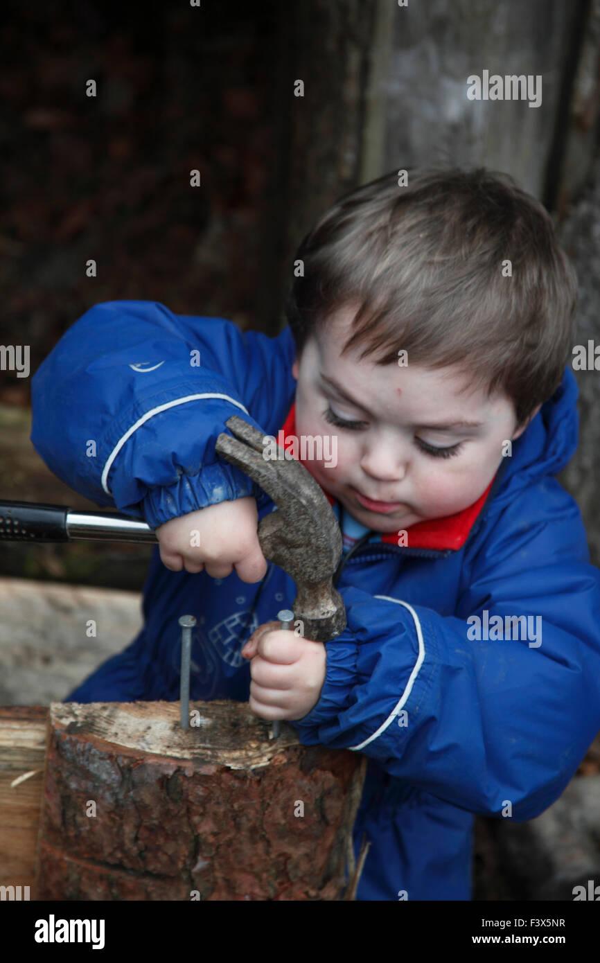 Kleiner Junge lernen, wie man Hammer verwenden, um Nagel ins Holz zu klopfen Stockbild