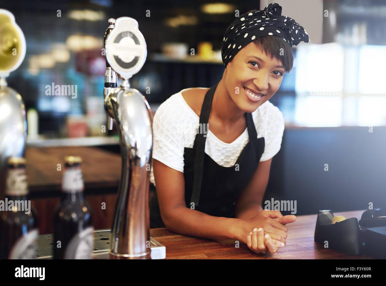 Attraktive junge afroamerikanische Kleinunternehmer gekleidet in ein Kopftuch und Schürze gelehnt auf dem Tresen Stockbild
