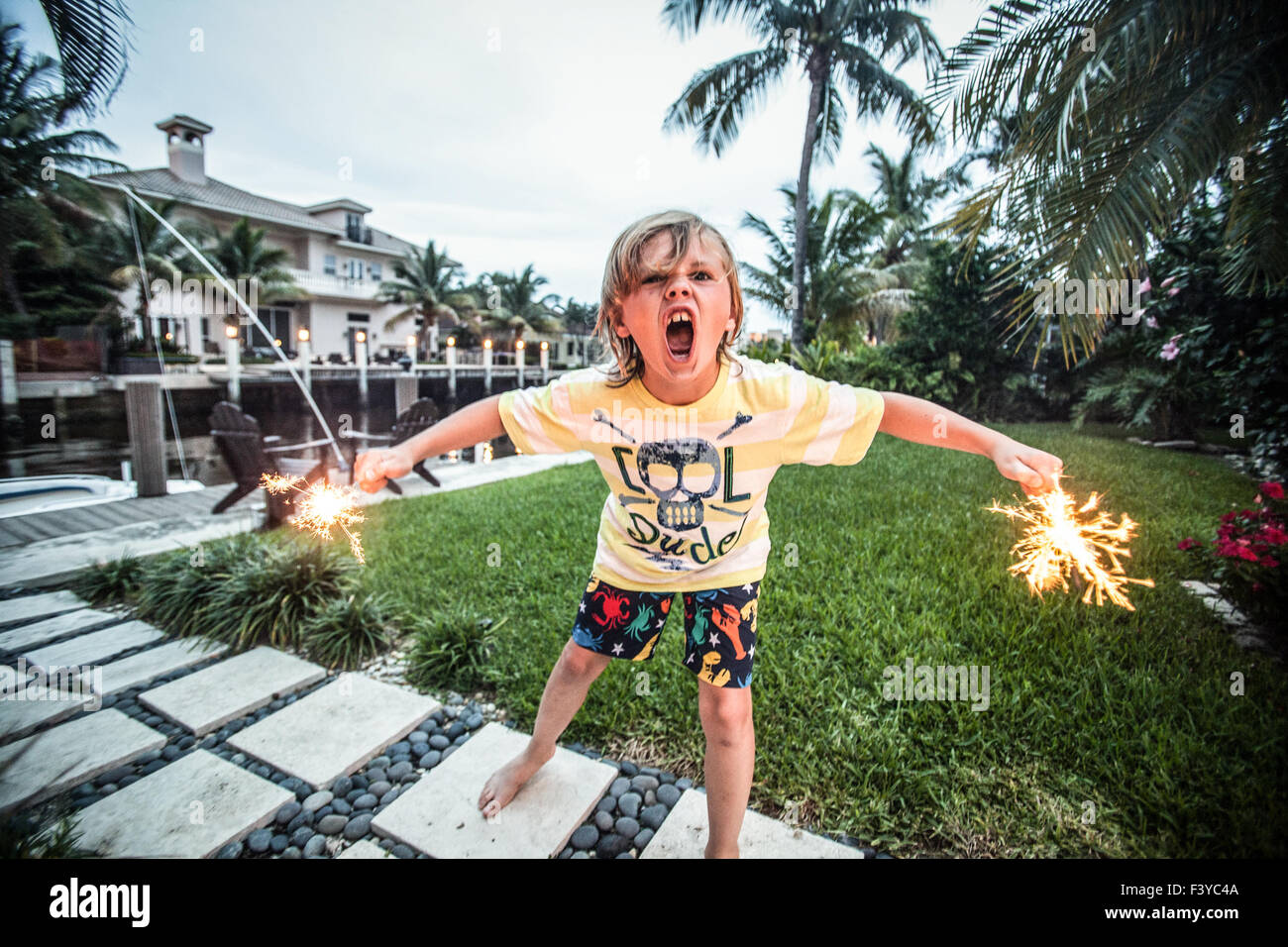 Ein kleiner Junge mit Wunderkerzen trägt eine coole dude-t-Shirt. Stockfoto