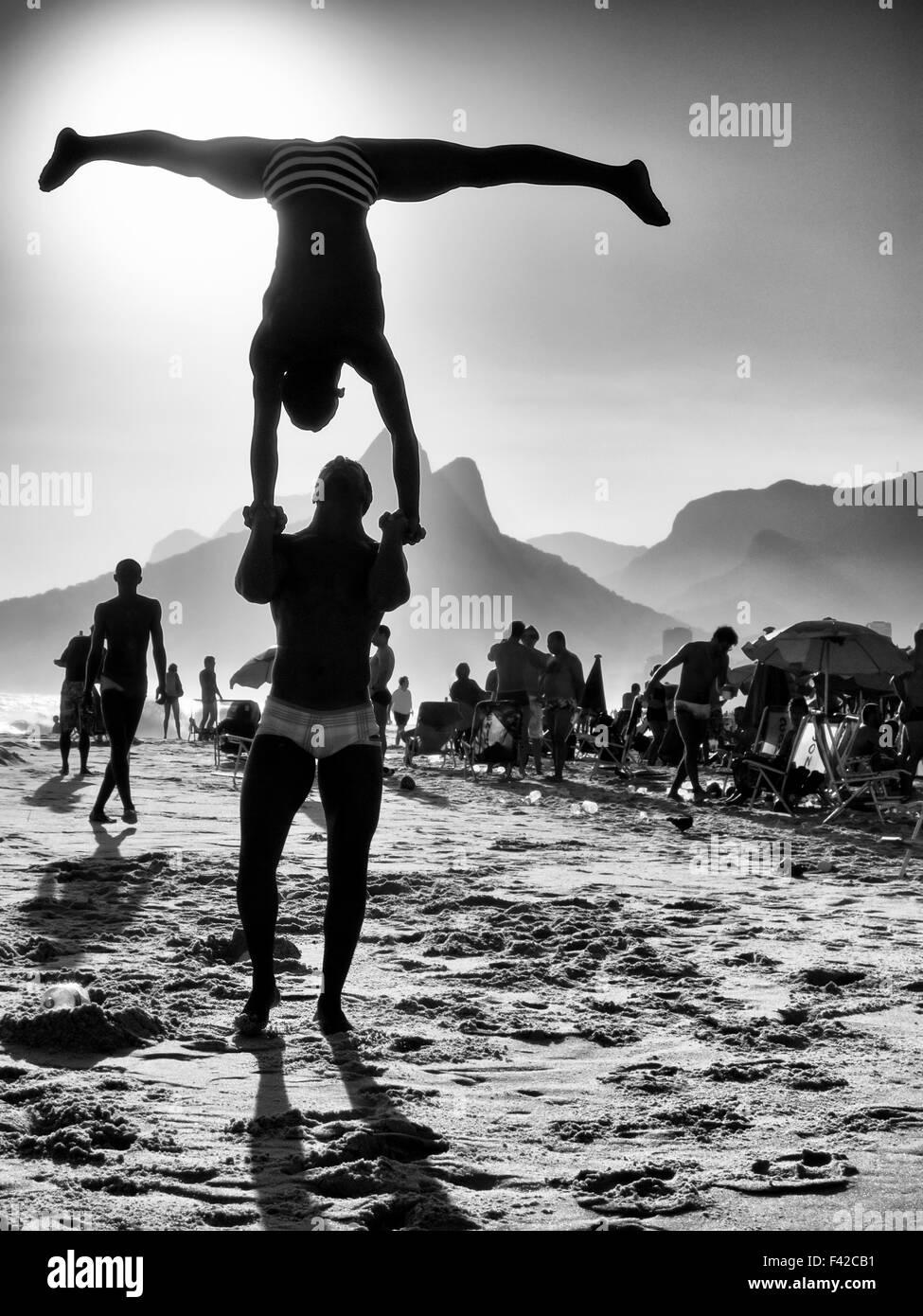 Silhouetten machen akrobatische Posen vor einer schwarz-weiß Sonnenuntergang Strand-Szene in Ipanema Strand Stockbild