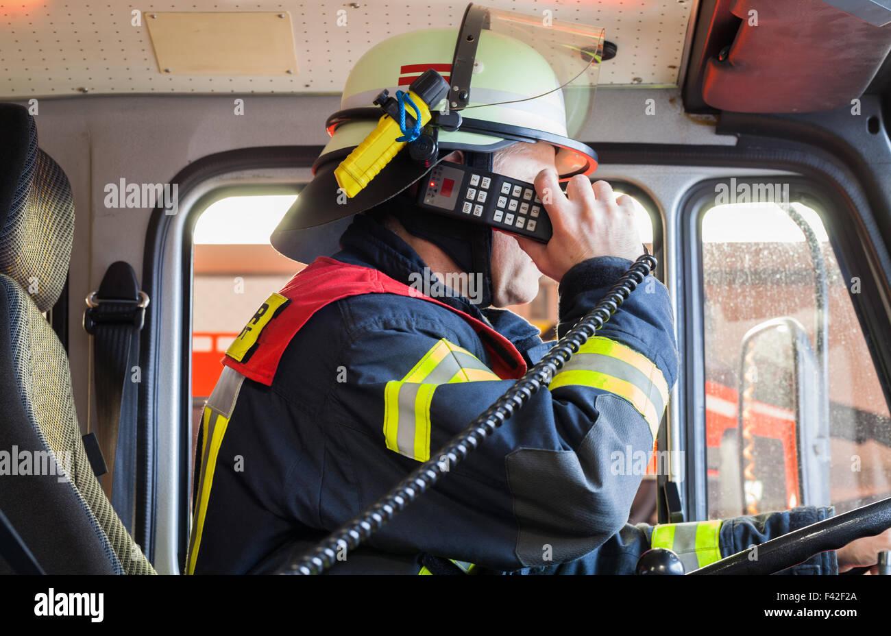 Feuerwehrmann in Aktion-Fahrzeug mit radio Stockbild
