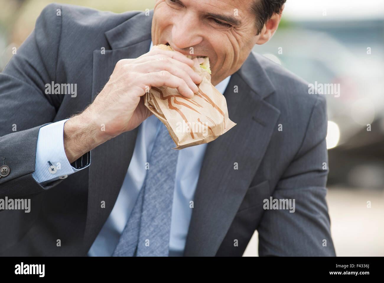 Geschäftsmann unterwegs Sandwich zu essen Stockbild