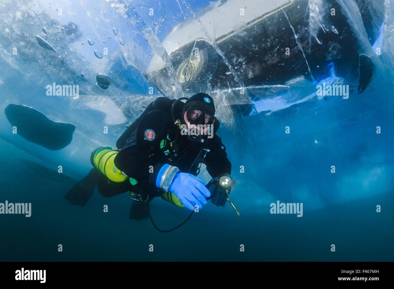 Taucher schwimmt unter transparente Eis (1m dick) mit Minivan oben sichtbar. Baikalsee, Russland, März 2012. -Modell Stockfoto