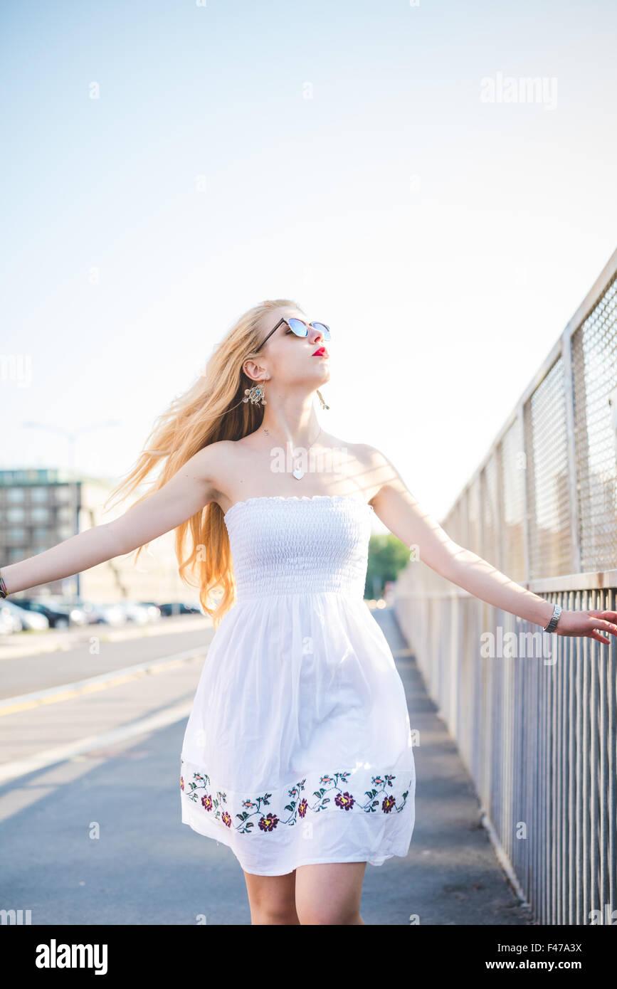 Knie Figur des jungen schönen kaukasischen langes blondes glattes Haar Frau zu Fuß in die Stadt, mit Blick Stockbild