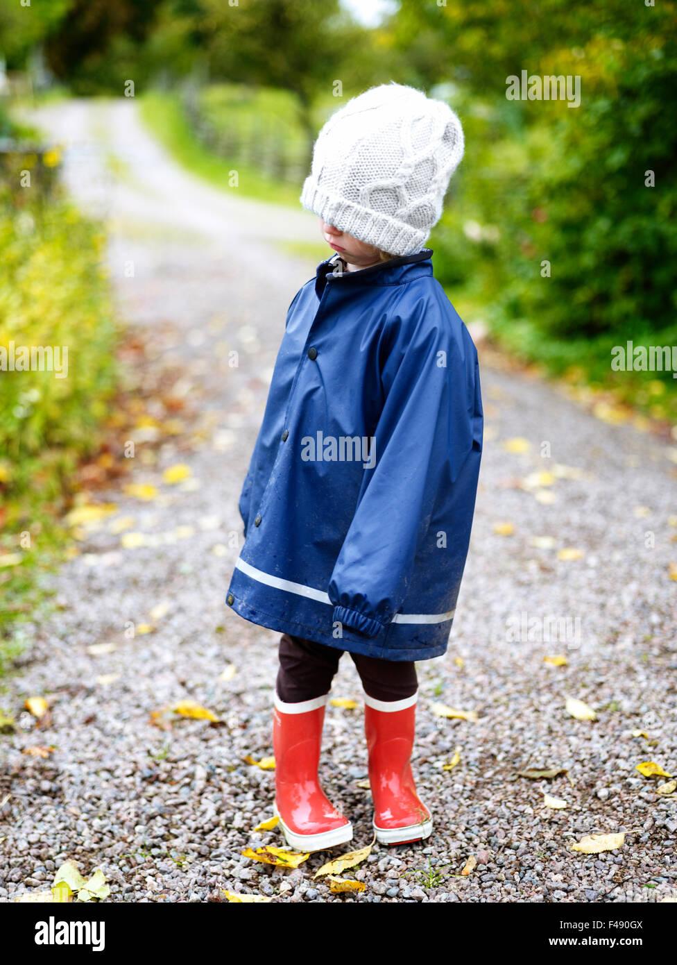 Ein enttäuscht Mädchen in einem blauen Regenmantel, Schweden. Stockbild