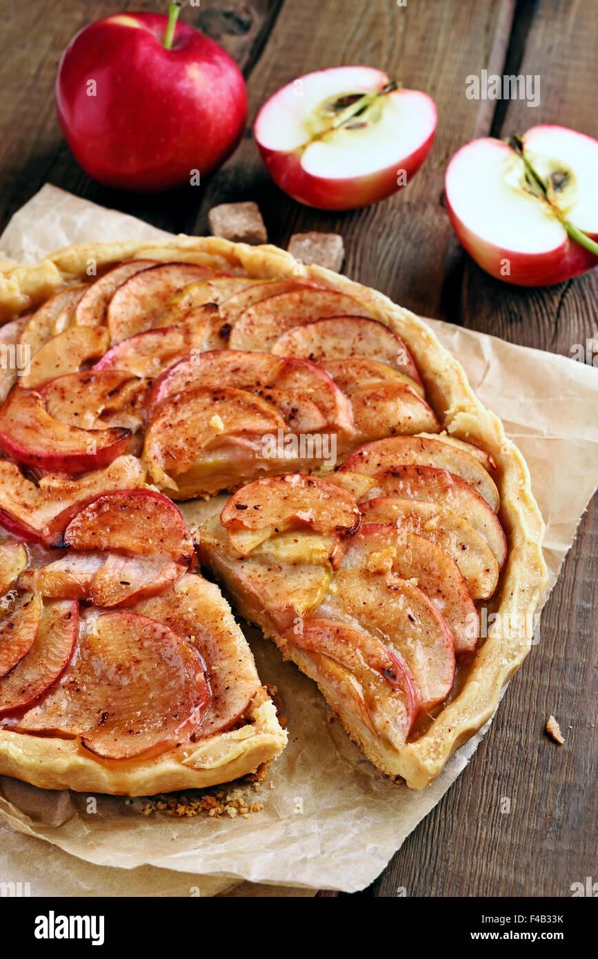 Obst-Apfelkuchen über Backpapier auf rustikalen Tisch Stockbild