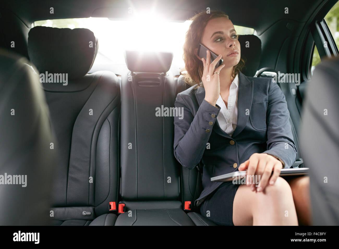 Geschäftsfrau mit Handy auf dem Rücksitz eines Autos. Weibliche Mitarbeiter telefonieren während Stockbild