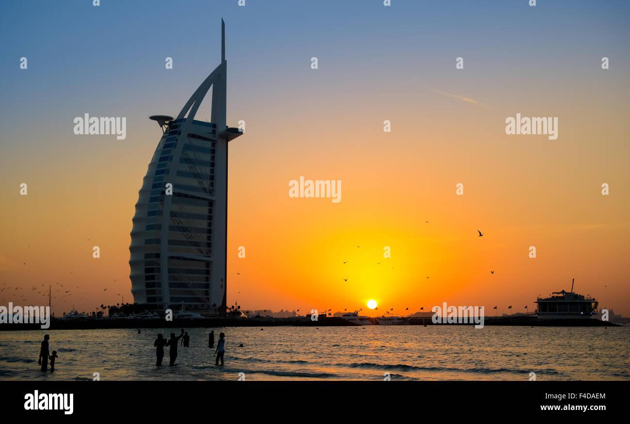 Hotel Burj Al Arab, Dubai im Sonnenuntergang mit Menschen im Wasser Stockbild