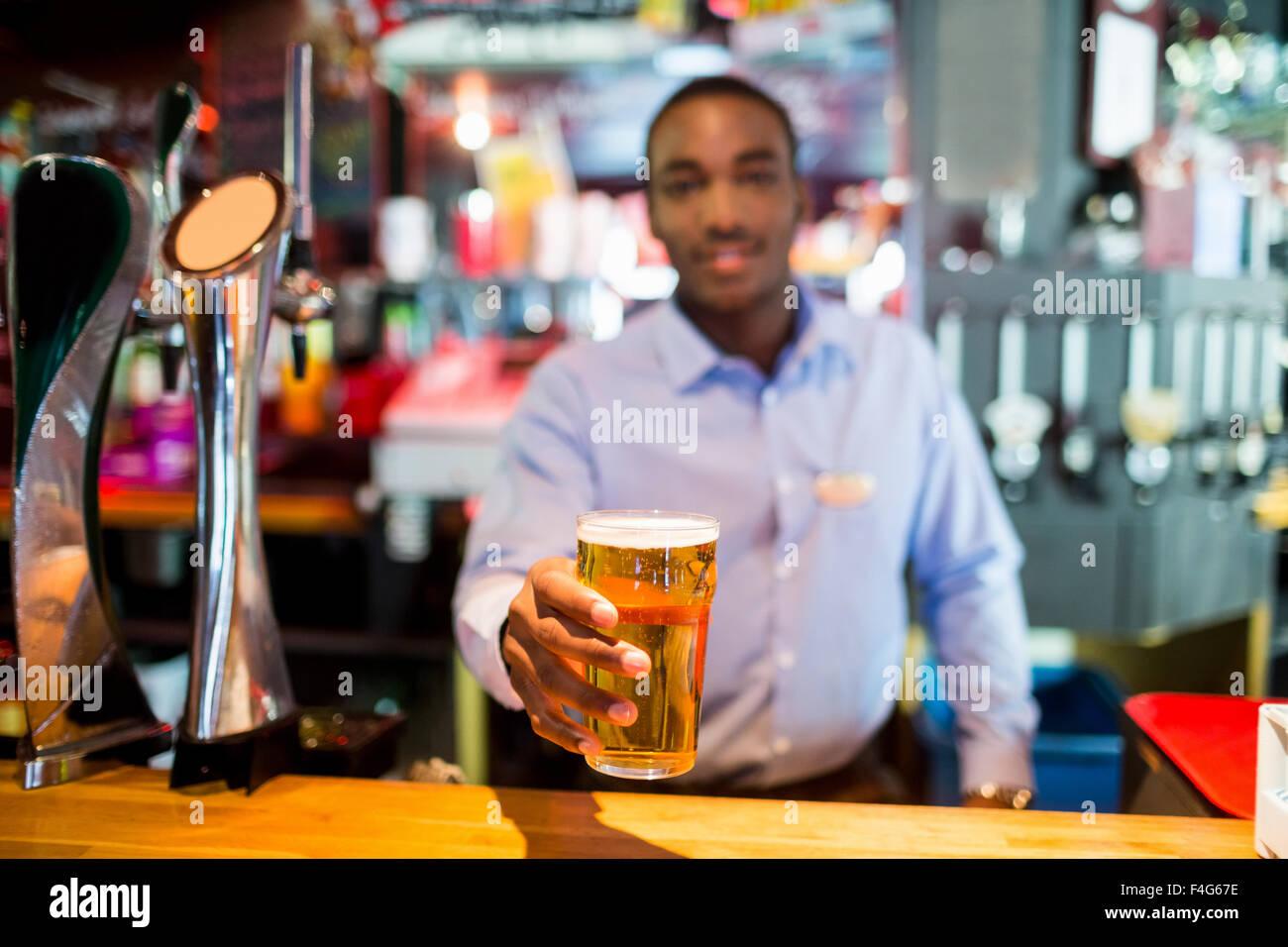 Glas Bier von Barkeeper serviert Stockbild