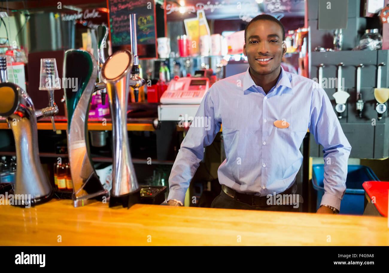 Barkeeper in der Nähe von Hahn posiert lächelnd Stockbild