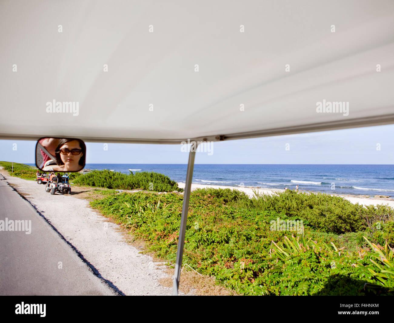 Touristen reiten Golf-Carts auf Rueda Medina, verläuft eine Hauptstraße, die von Playa Norte nach Punta Stockbild